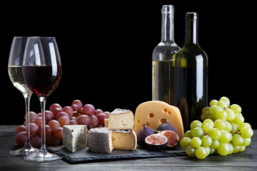 Ostbricka med fikon, vindruvor och vin – både vitt och rött.