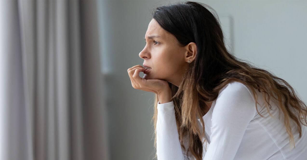 Kvinna som sitter och funderar på en soffa