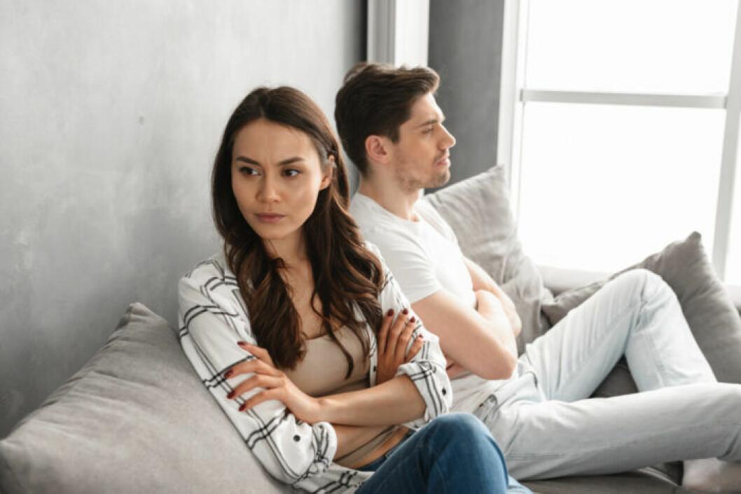 Ett par sitter i en soffa och tittar argt åt varsitt håll