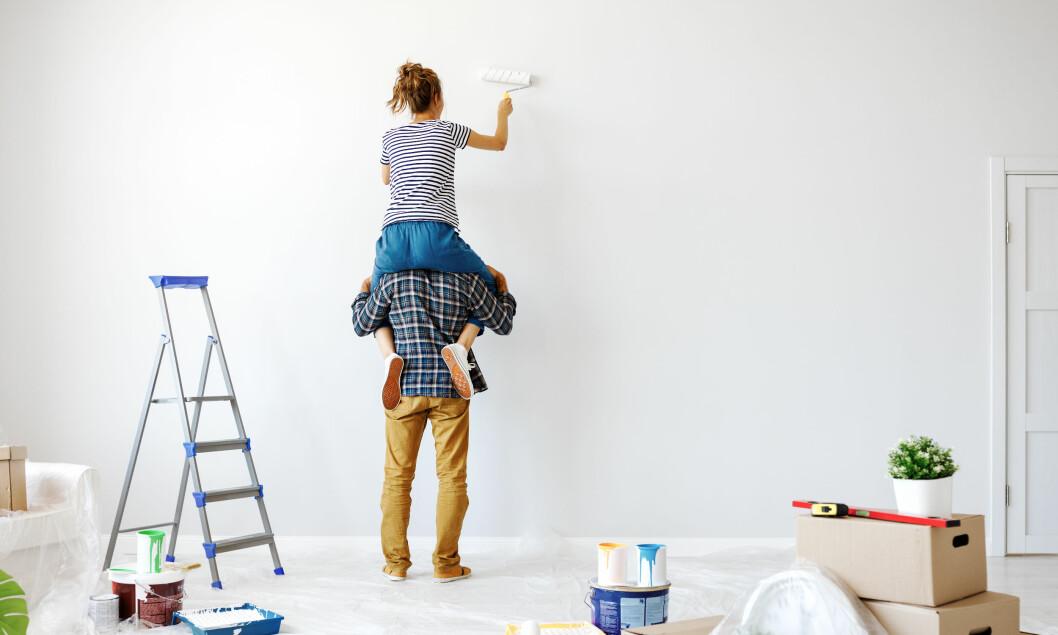 Kvinna på en mans axlar som målar om väggen