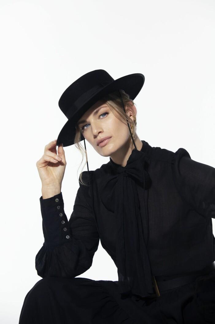 Nygårds Svart blus med tillhörande rosett kombinerat med en svart hatt