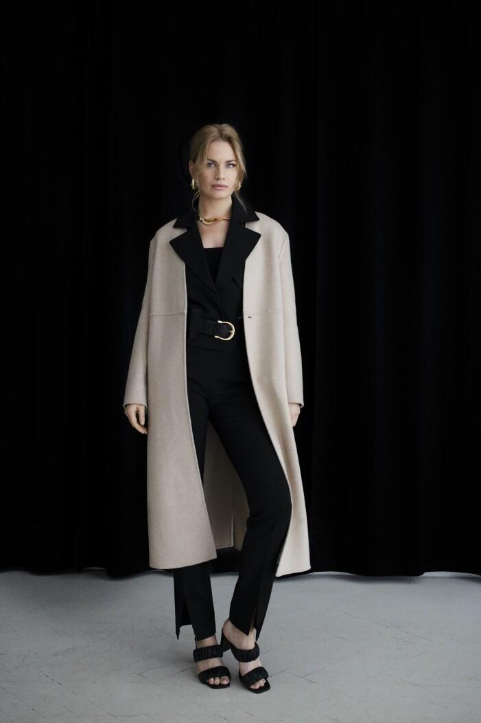 Stylein Snygg beige kappa med svart skjorta och svarta kostymbyxor