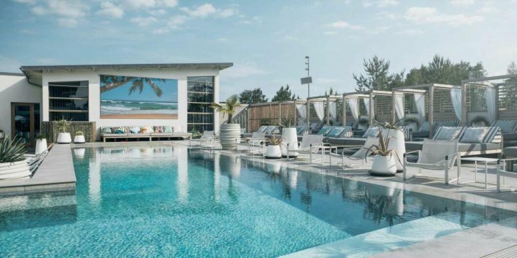 En stor pool med solstolar och cabanas runt omkring