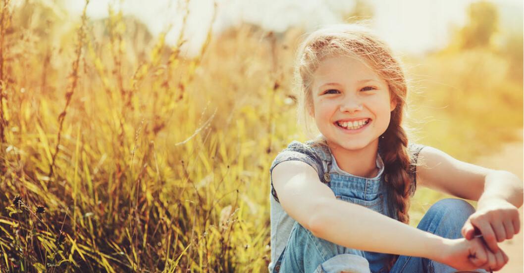 Glad flicka som sitter ute i gräset