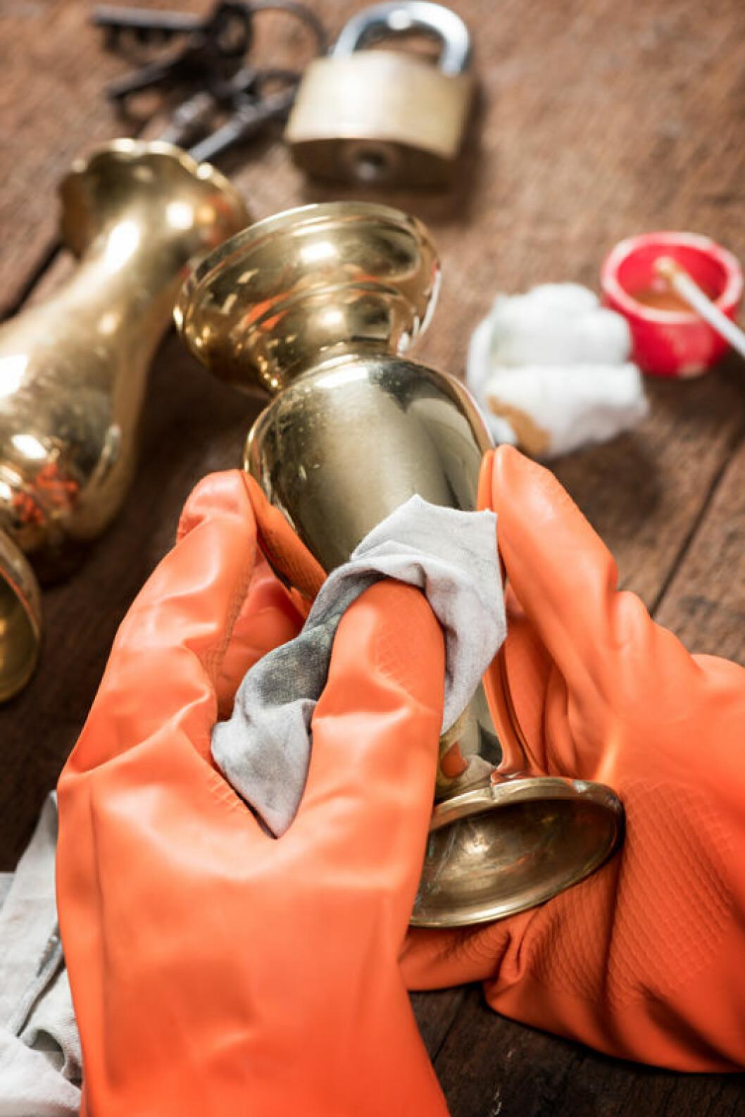 Person med orangea handskar putsar gammalt kopparföremål.