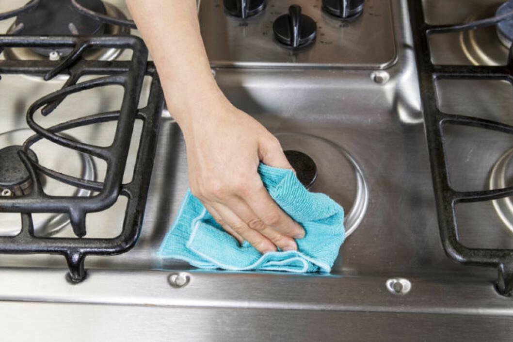 Kvinna torkar av gasspis med trasa.