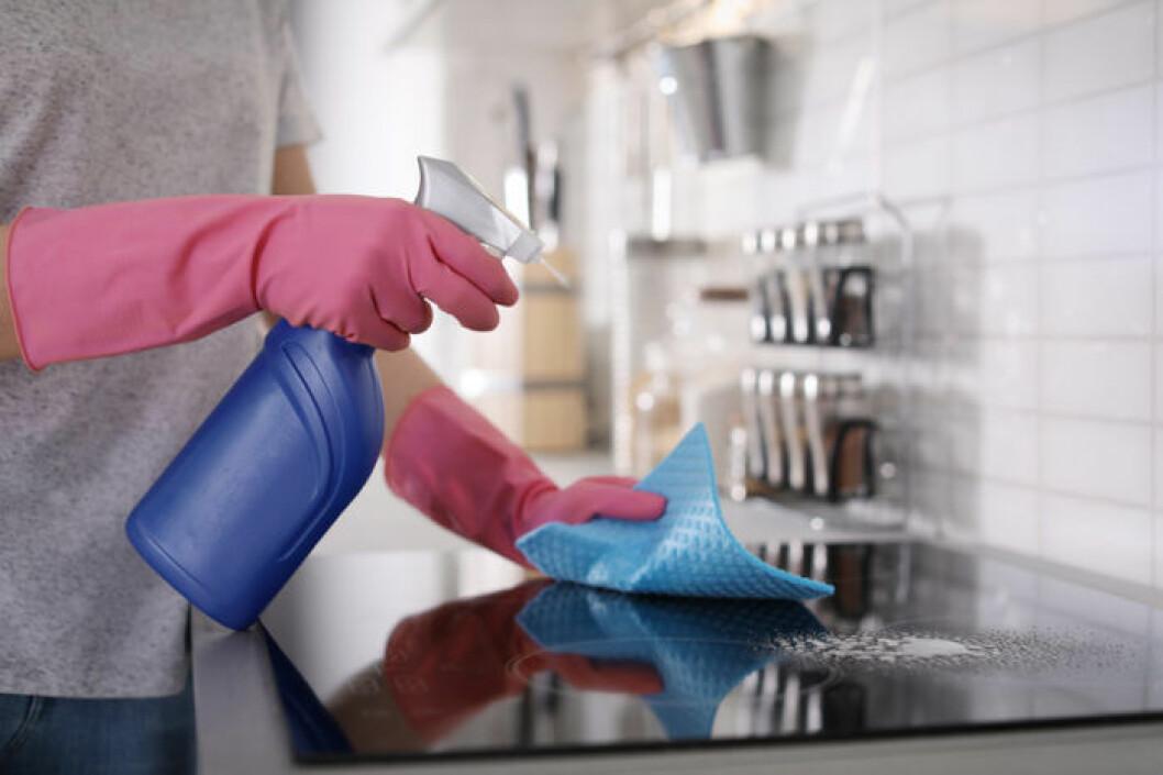 Kvinna med sprayflaska gör rent spishäll.