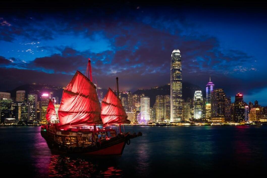 Hong Kong på kvällen med asiatisk röd båt