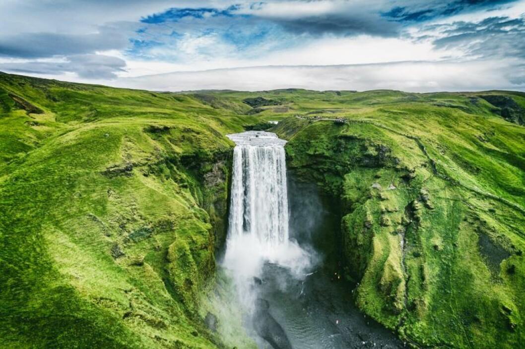Vybild över grönt landskap med vattenfall