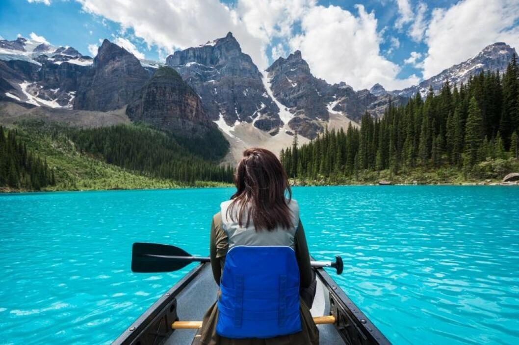 Kvinna paddlar kanot på sjö bland bergen i Kanada