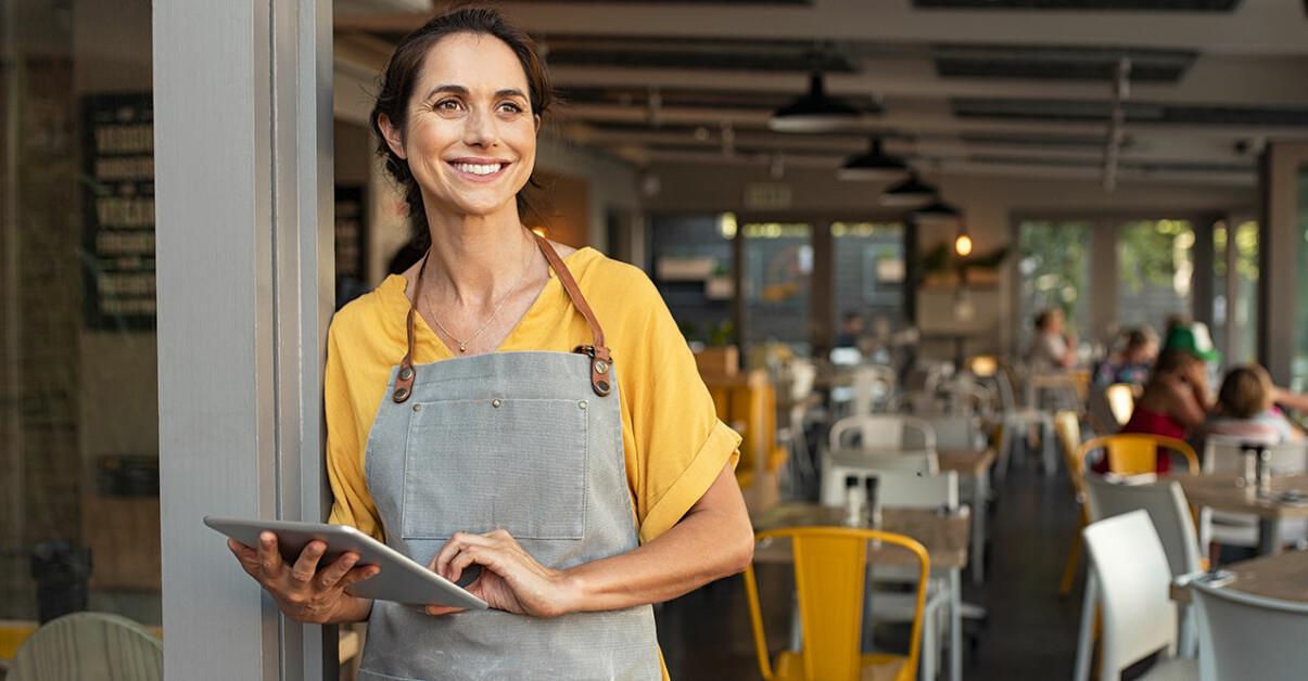 Kvinna på restaurang ler och blickar ut