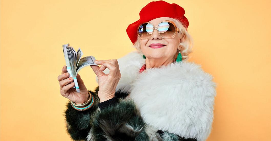 en dam med röd basker, solglasögon och päls håller i en bunt med pengar och ler