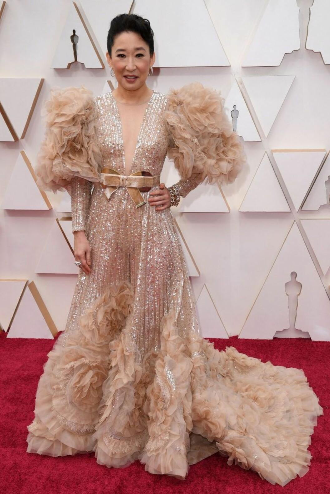 Sandra Oh i guldig klänning med fjädrar på röda mattan