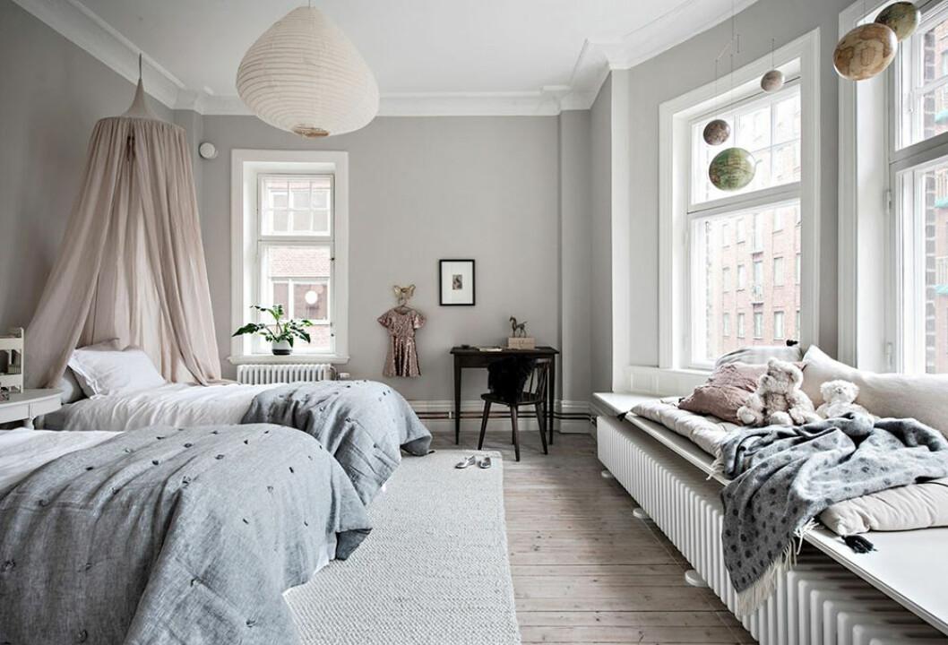 Vacker inrett barnrum med ljusrosa sänghimmel och läshörna