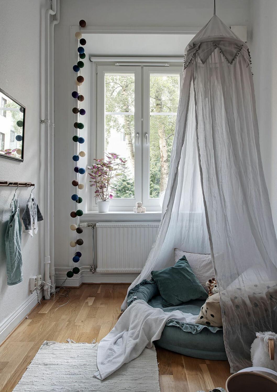 Mysig läshörna i barnrummet med sänghimmel och kuddar