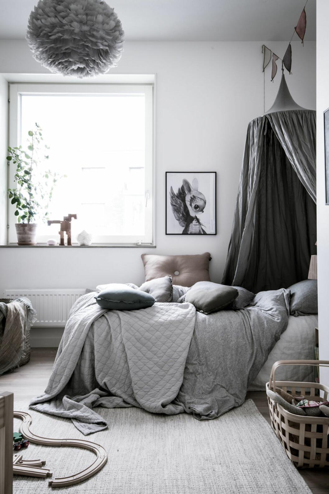 Barnrum i grått med sänghimmel över sängen
