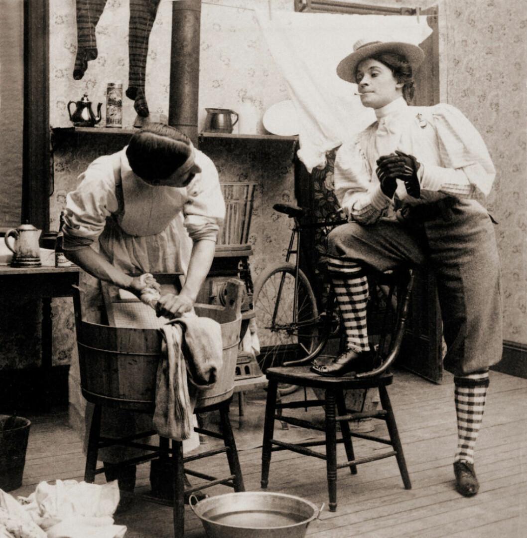 Kvinna som röker iklädd knickers och man iklädd kjol som tvättar.