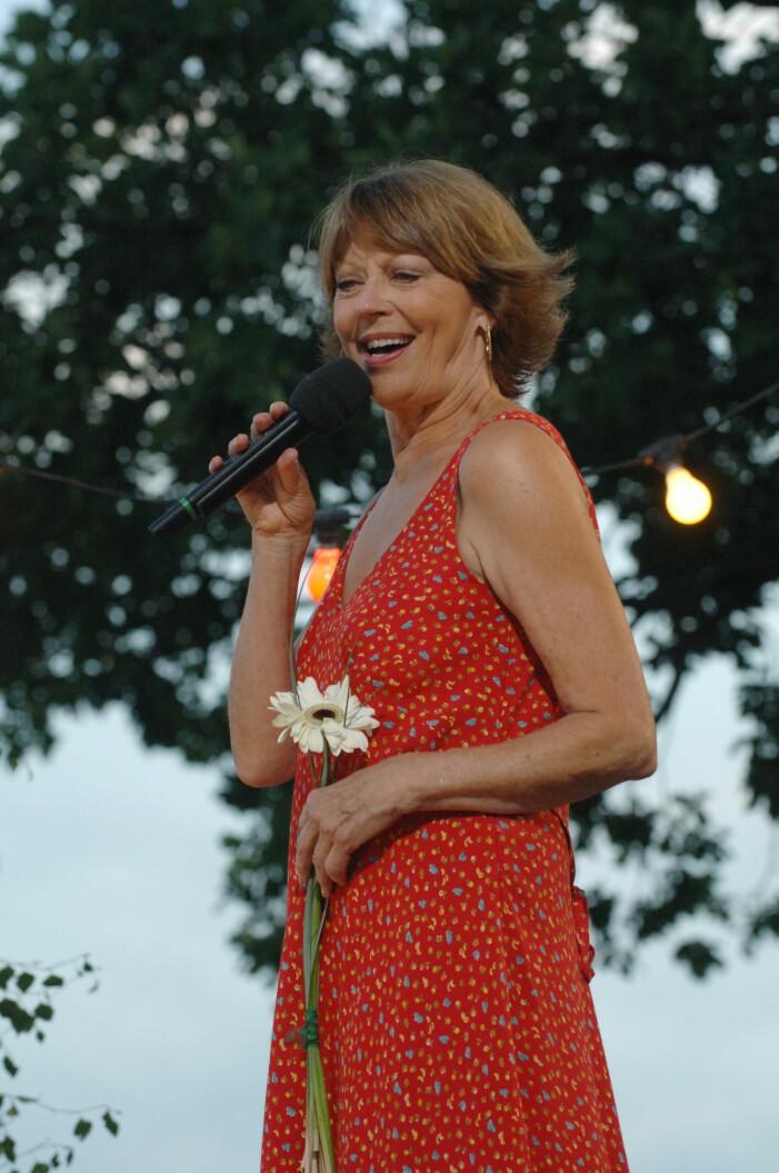 Lill Lindfors i en röd blommig klänning på allsång på skansen
