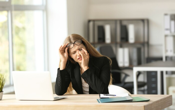 Kvinna vid dator med huvudvärk.