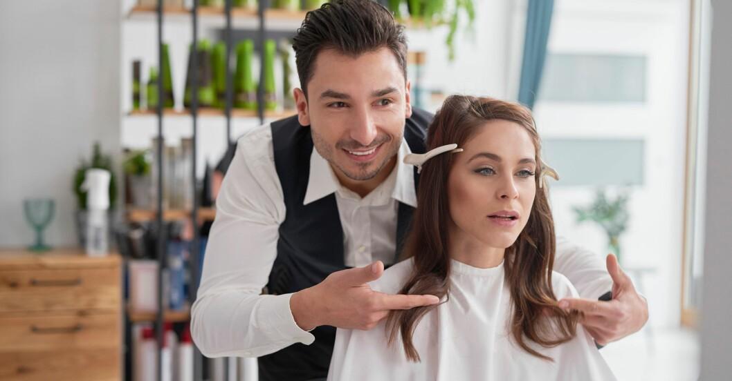 Manlig frisör med kvinnlig kund.