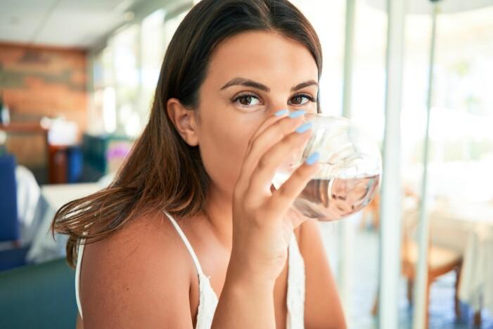 Kvinna dricker vatten.