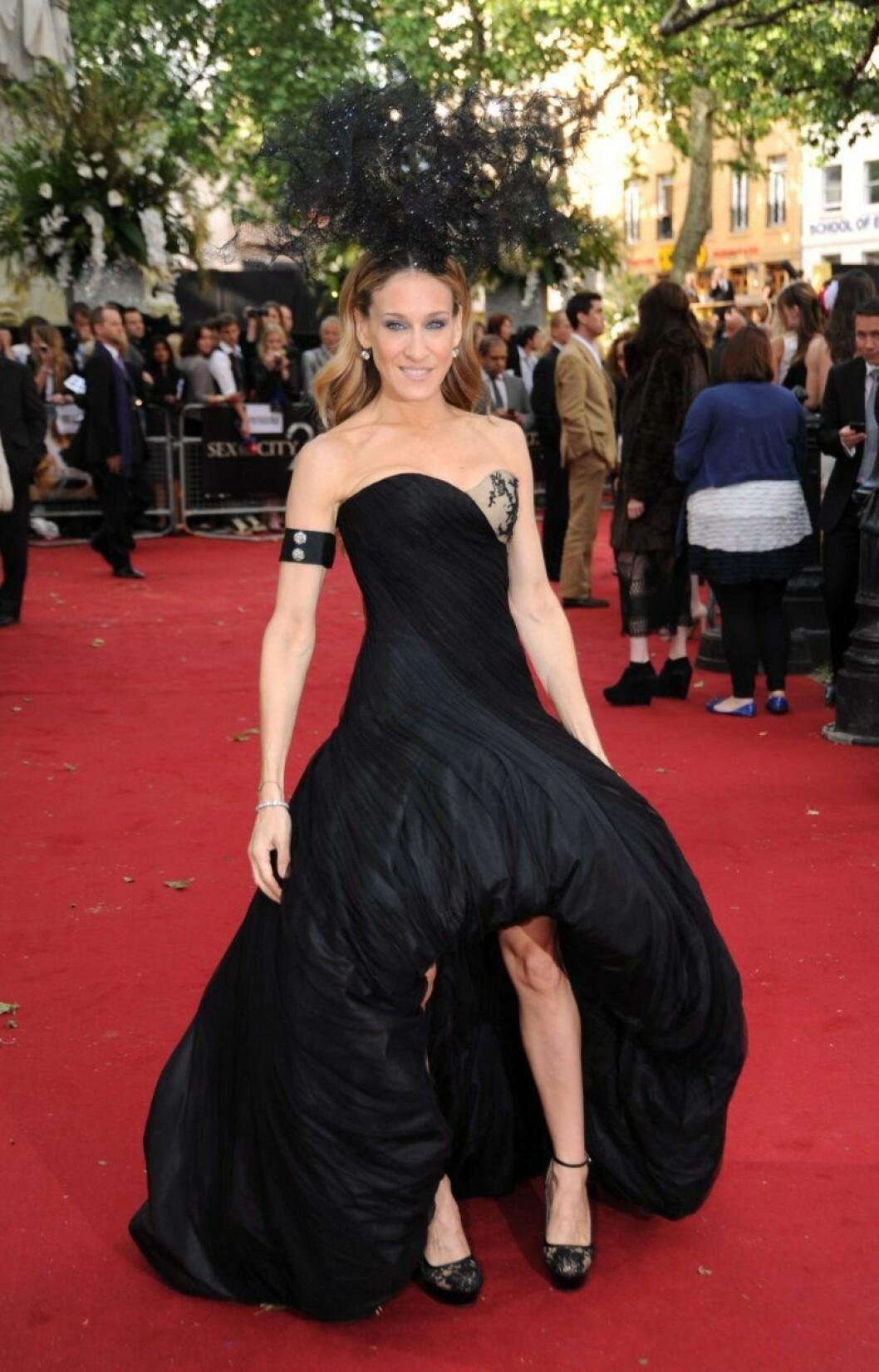 Sarah Jessica Parker på röda mattan i en svart, axellös klänning med en stor hårdekoration.