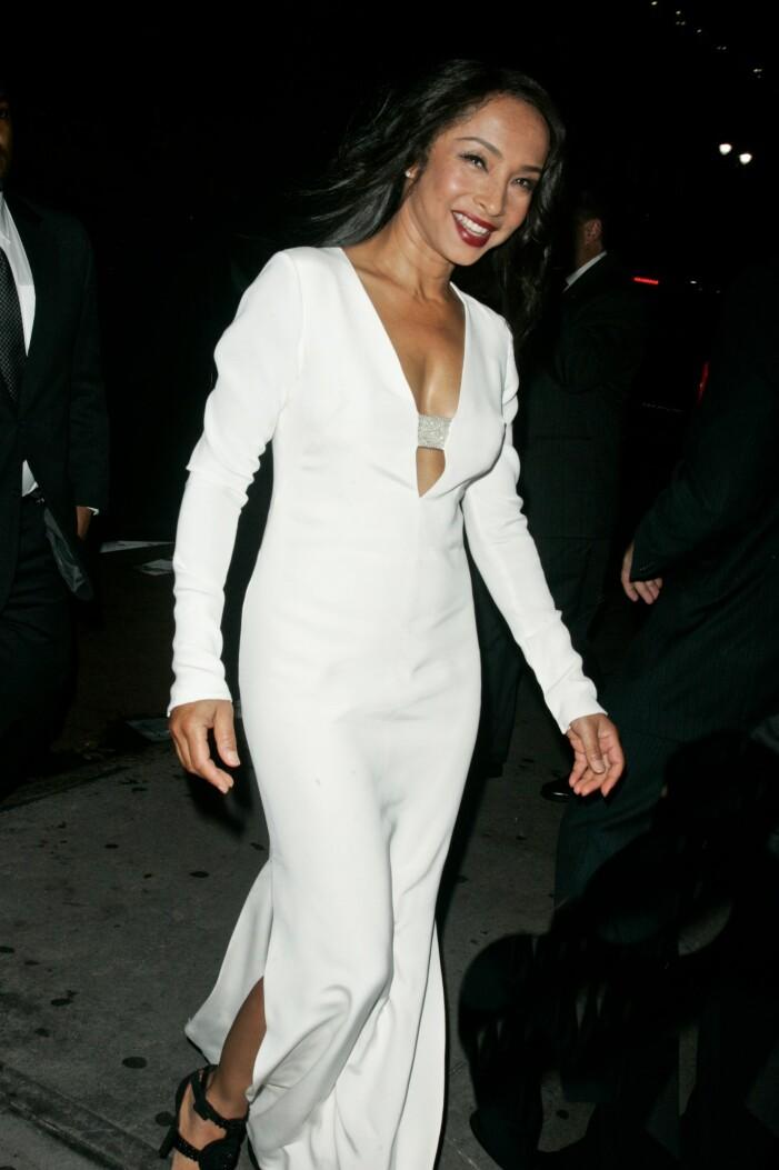 Sade i en vit klänning med djup v-ringning
