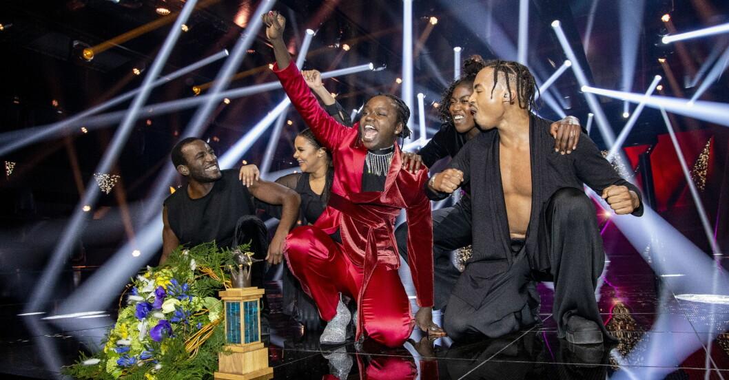 Tusse Chiza i röd kostym gör ett glädjerop i finalen på Melodifestivalen.