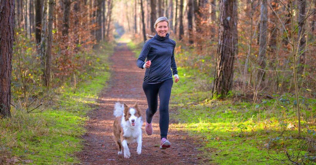 Glad kvinna springer i skog med hund.