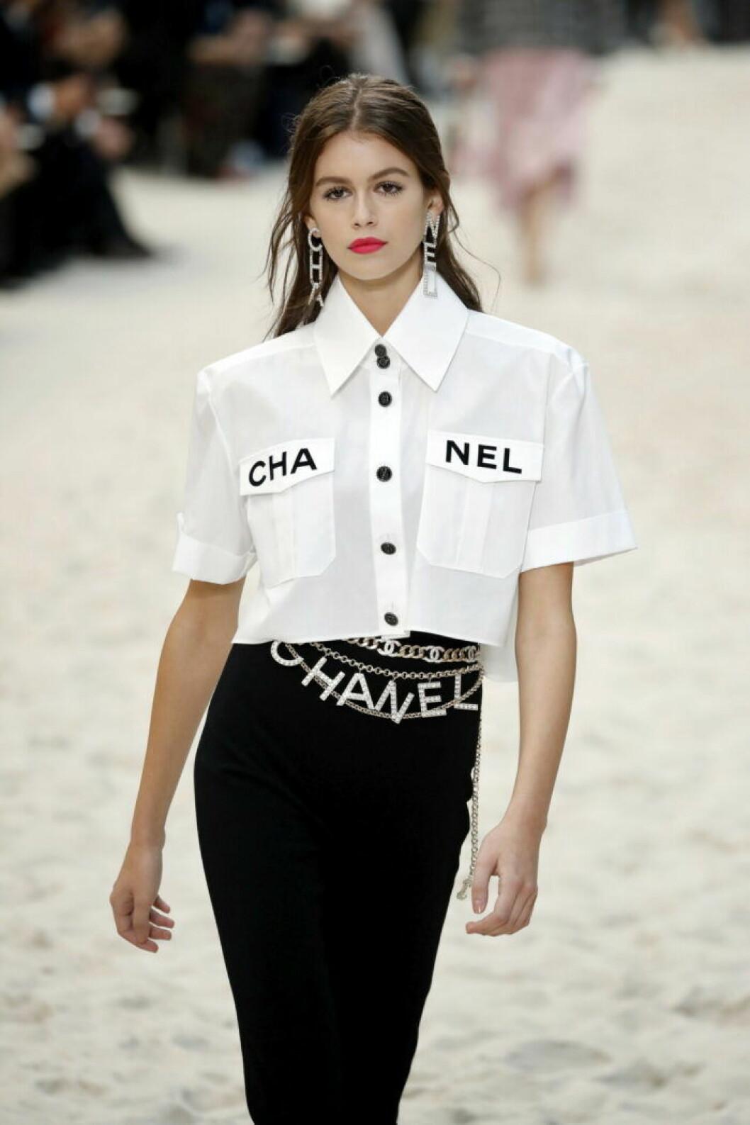 Karl Lagerfelds visning för Chanel 2019, vit skjorta med chaneltryck och ett glittrigt chanelbälte.