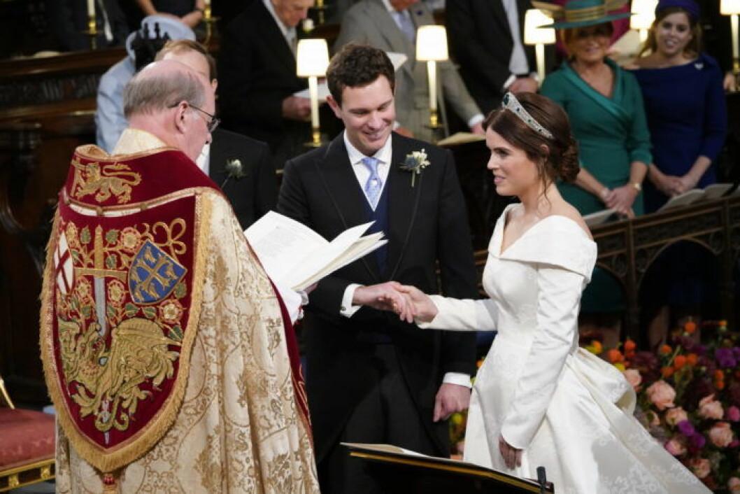 Jack Brooksbank och prinsessan Eugenie står framför prästen vid altaret i St Georges Chapel