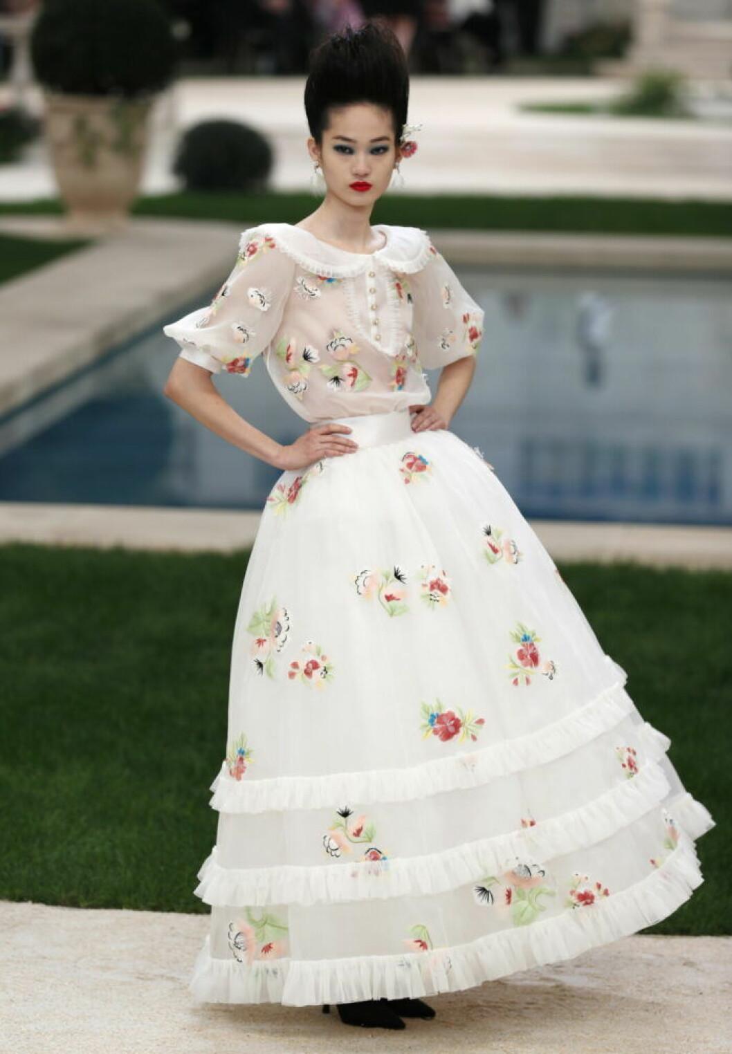 Karl Lagerfelds design under Chanelvisningen 2019, en vit sekelskiftesklänning med blommor.