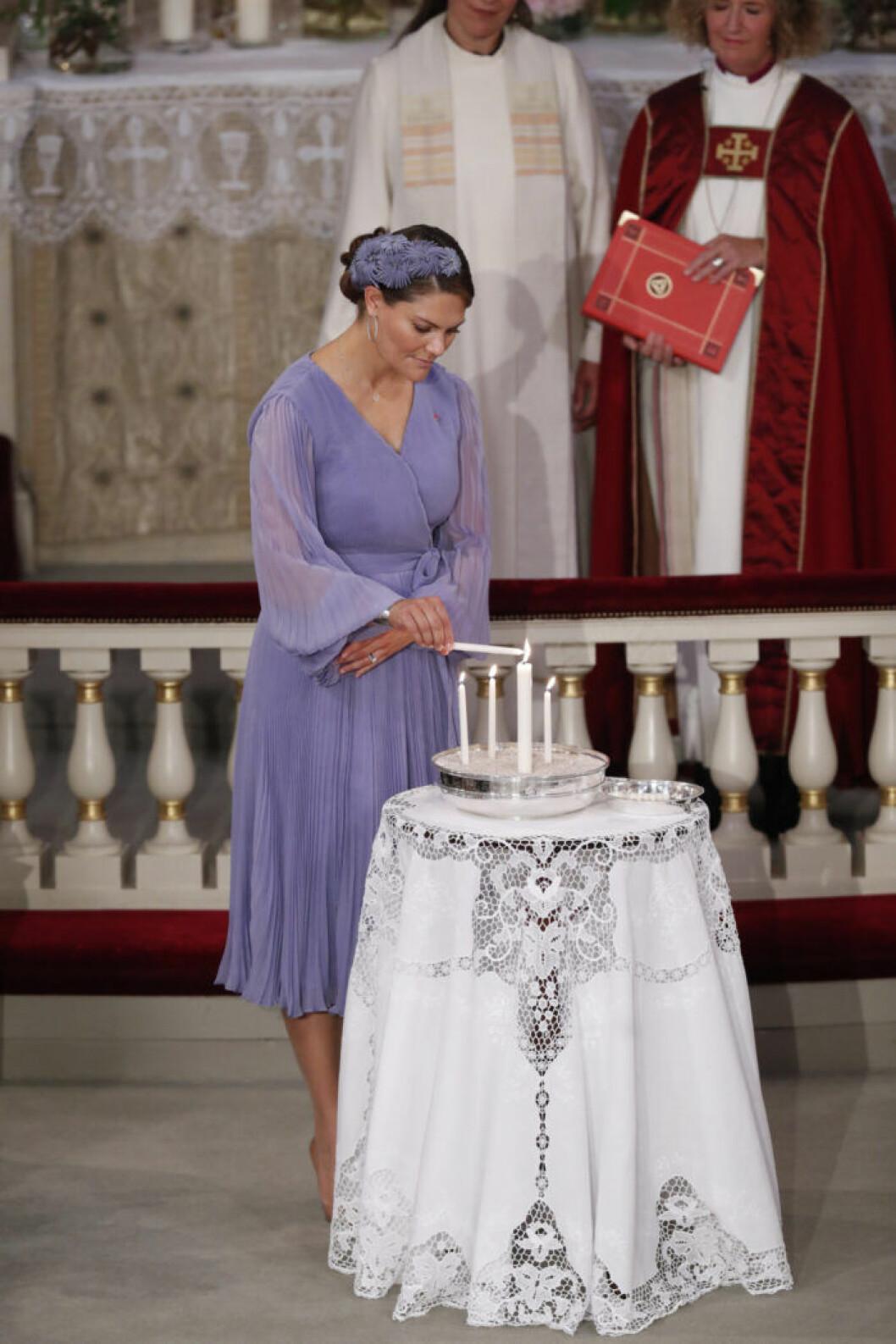Victoria tänder ett ljus framme vid altaret