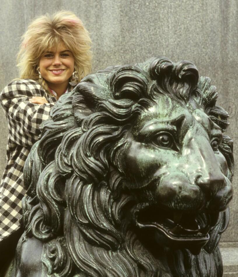 Pernilla Wahlgren i fluffig frilla på ett bronslejon.