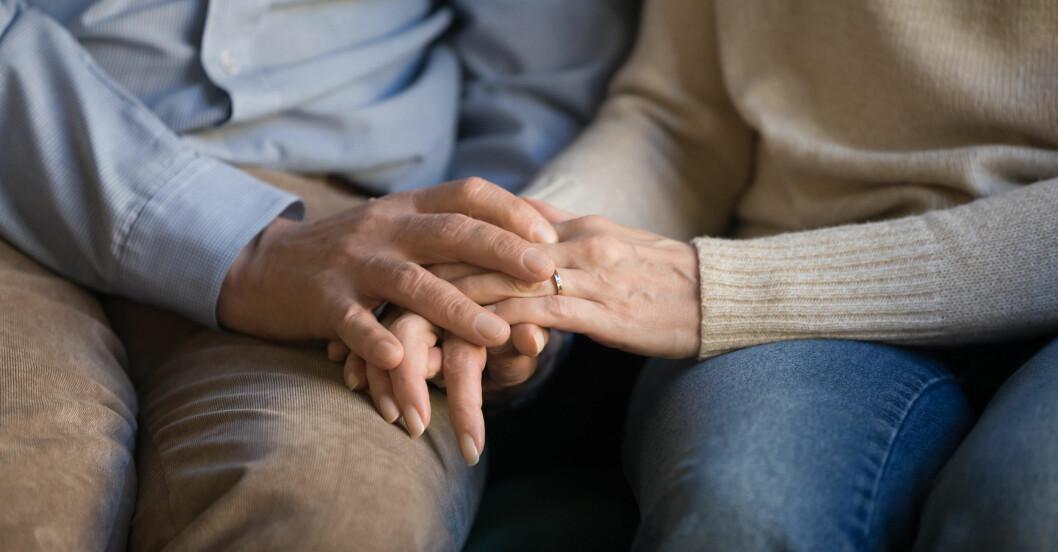 Ett äldre par håller handen.