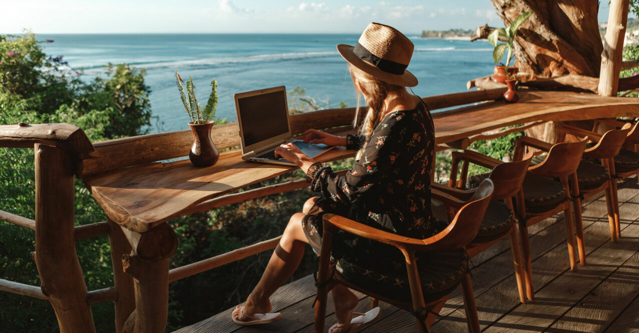 kvinna vid dator utomhus vid havet