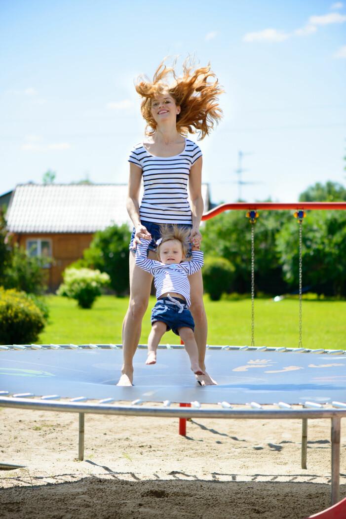 En kvinna hoppar studsmatta med sitt barn