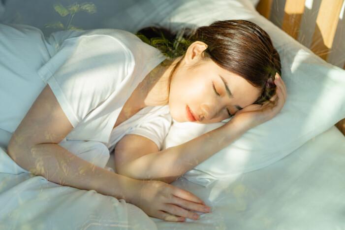 Kvinna vaknar av solen i ansiktet
