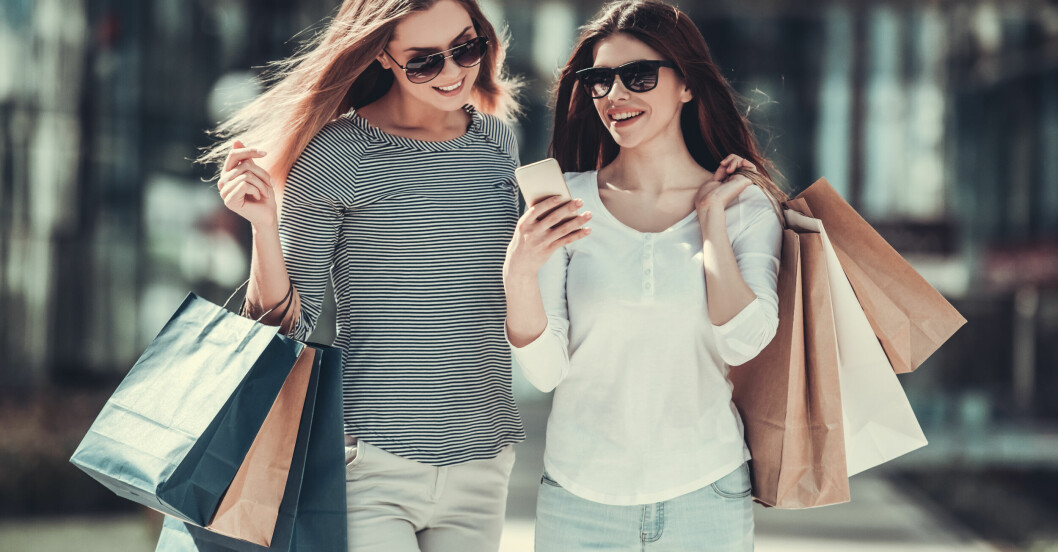 Två glada kvinnor på shoppingrunda