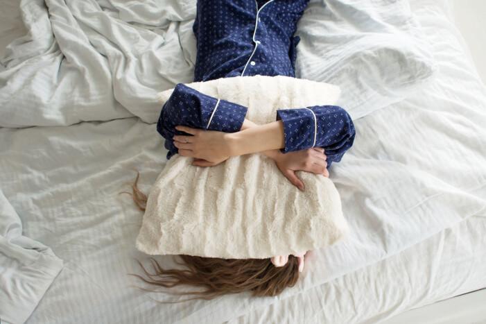 kvinna dämpar ljuset från solen med hjälp av en kudde