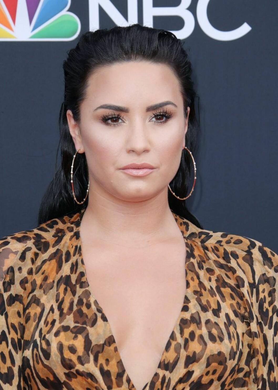 Demi Lovato med bakåtslickat hår och stora örhängen