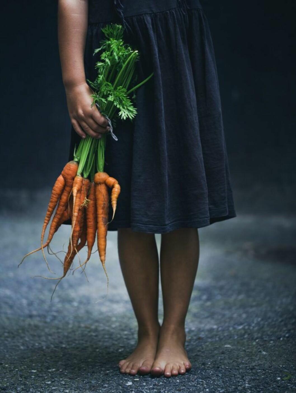 Flicka med morötter i handen