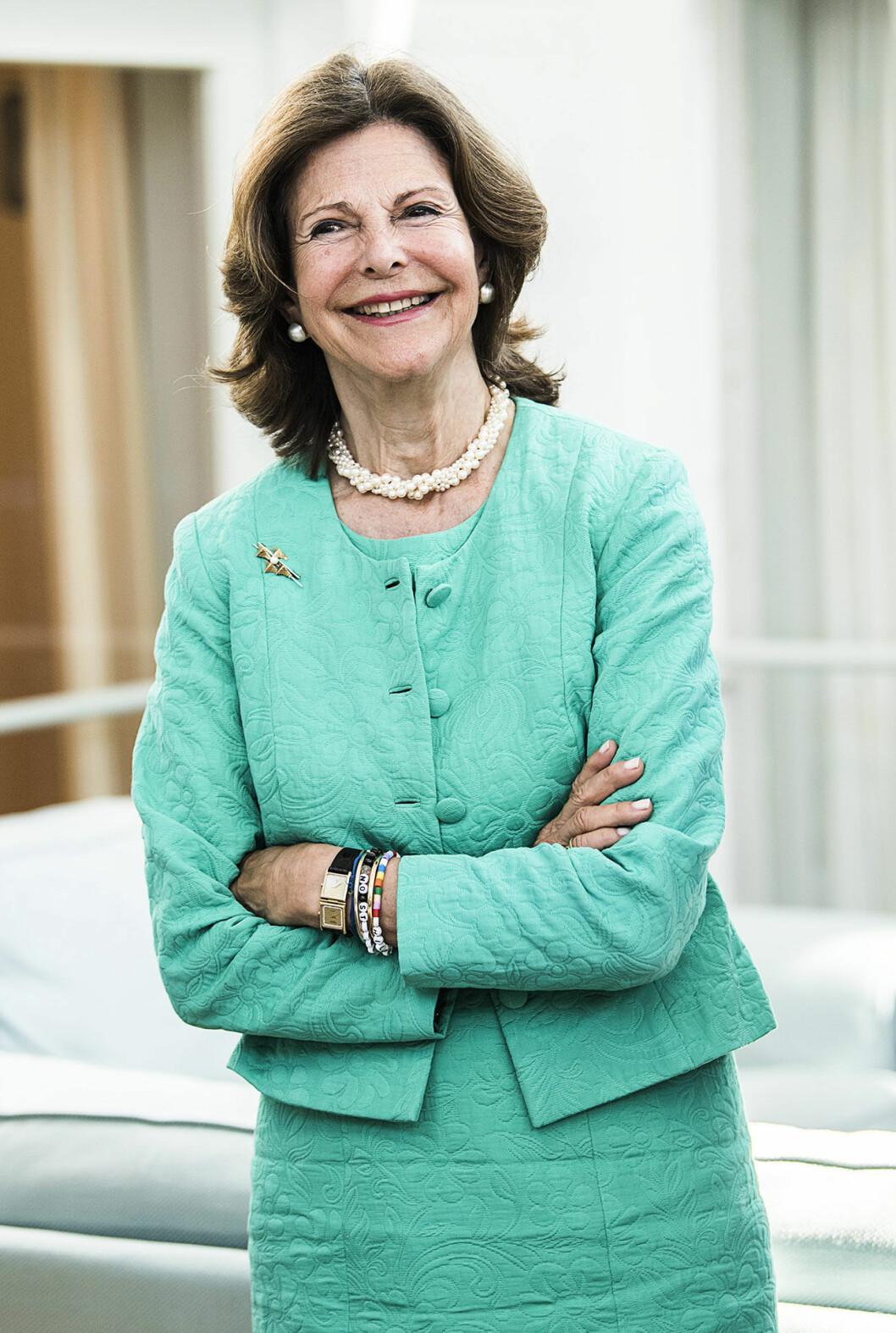 Drottning Silvia i mintgrön dräkt med klocka med dubbla urtavlor.