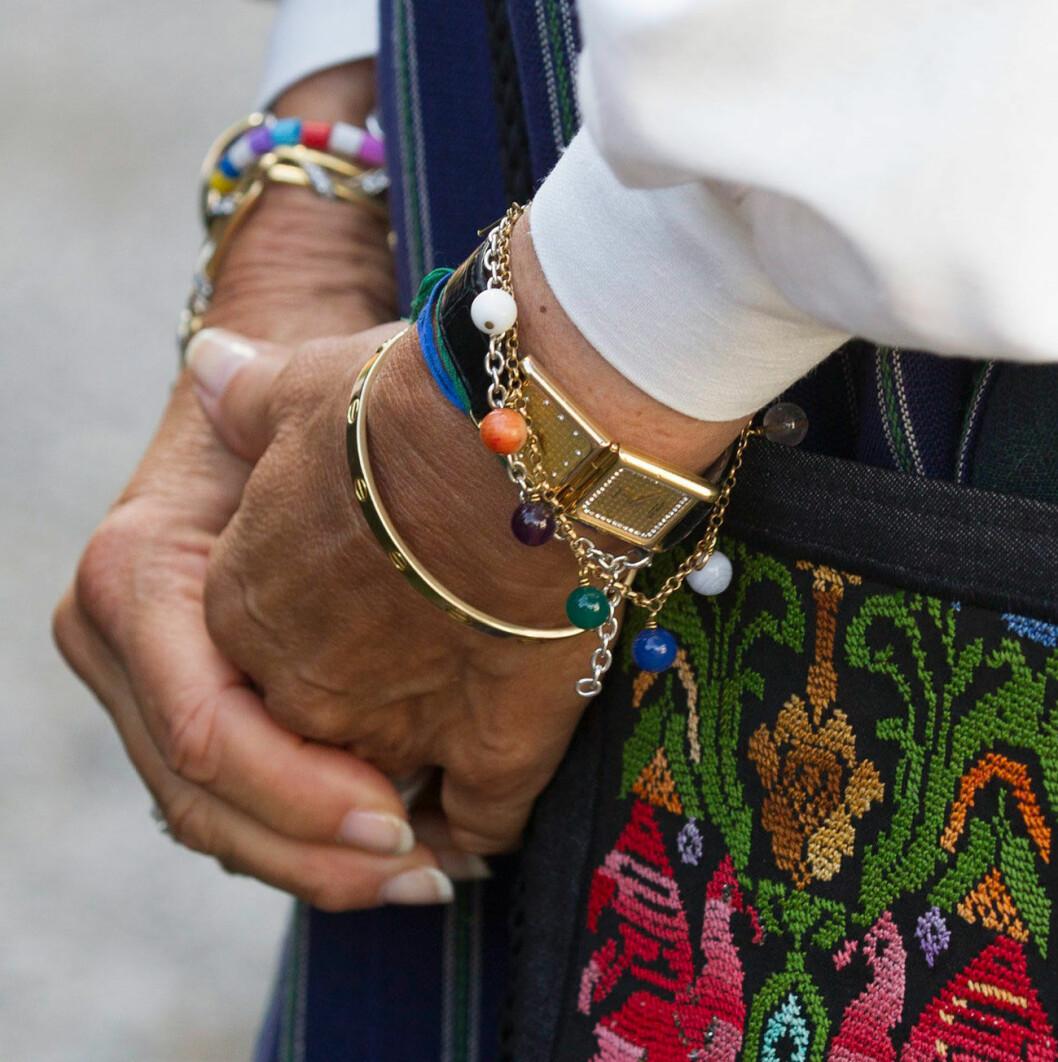 Drottning Silvia, klädd i högtidsdräkt, med klocka med dubbla urtavlor.