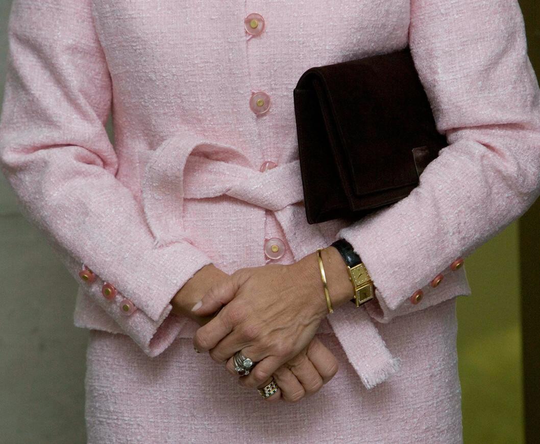 Drottning Silvia i rosa dräkt med klocka med dubbla urtavlor.