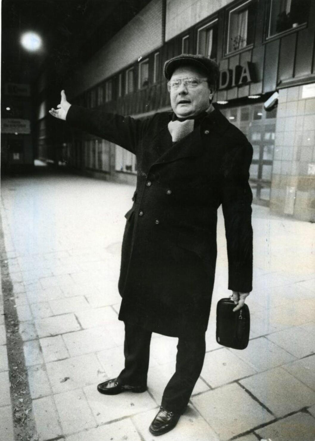 En man i svart rock och keps pekar med hela handen