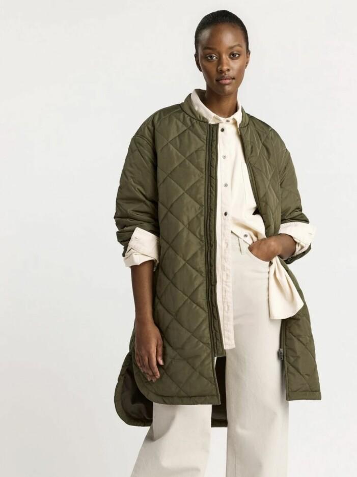 outfit med vita plagg och grön kappa