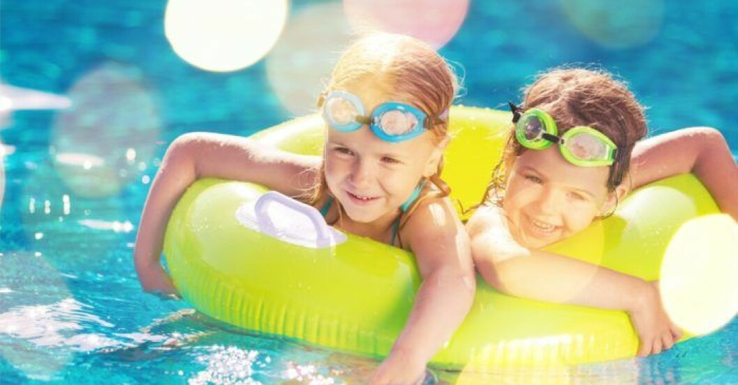 Barn badar och leker i poolen på somamren.