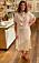 Soraya Lavsani i sett med topp och kjol i beige. Blusen är ärmlös och draperad framtill.