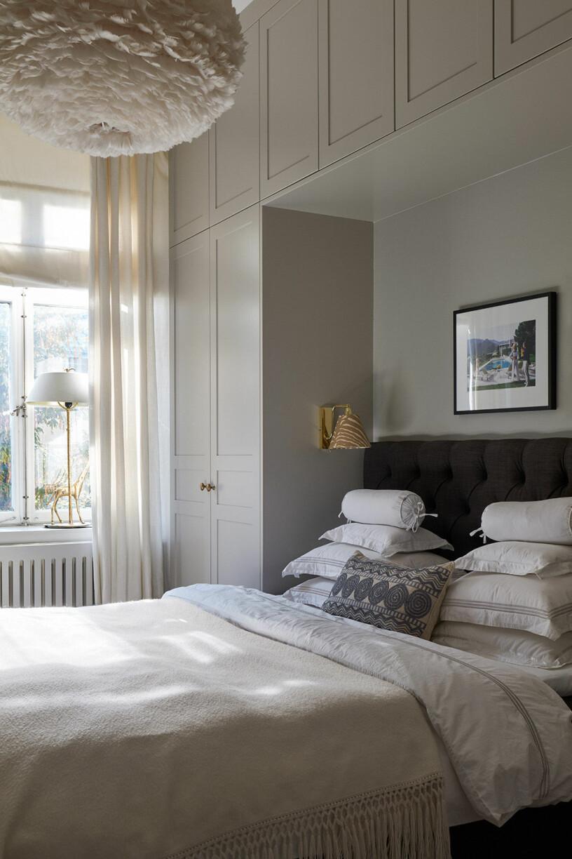 sovrum med platsbyggd garderob runt sängen i beige